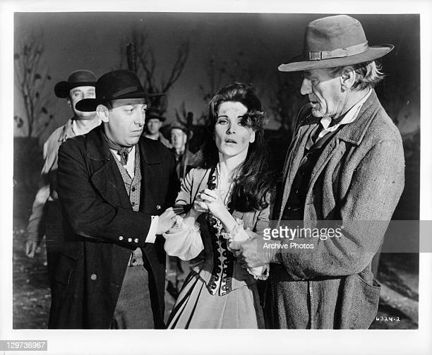 Debra Paget being held by two unidentified men in a scene from the film 'Haunted Palace' 1963
