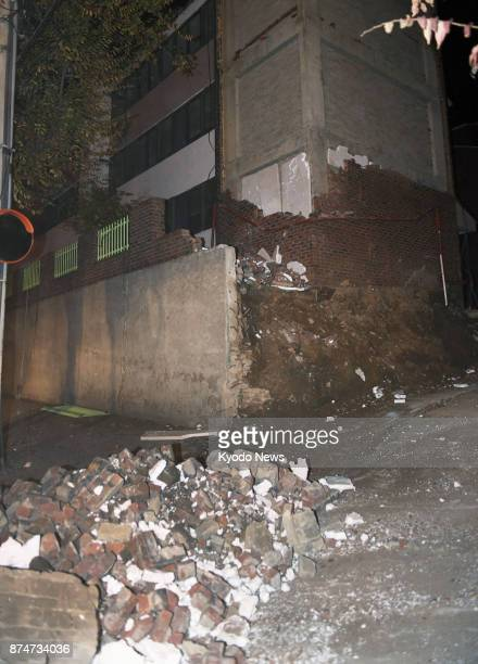 Debris and a collapsed brick wall litter the area outside a building in Pohang on Nov 15 after the southeastern South Korean city was rocked by a...