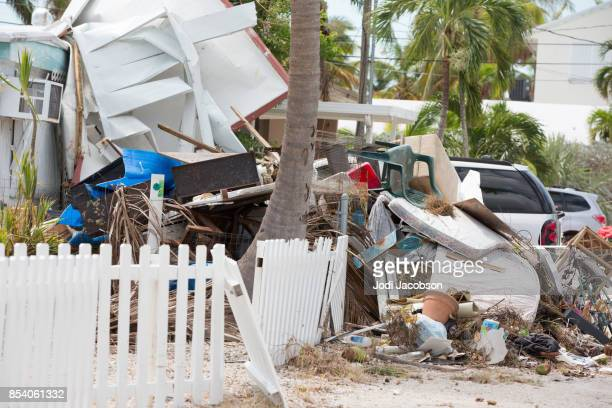 Debris and trash left in front of homes on residential street in the aftermath of a hurricane in Florida Keys