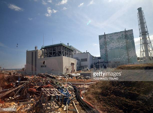 Debris are scattered before the sixth reactor building of stricken Tokyo Electric Power Co Fukushima Daiichi nuclear power plant to the journalists...