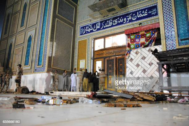 Debris are seen on the ground as Pakistani soldiers cordon off the shrine of 13th century Muslim Sufi Saint Lal Shahbaz Qalandar after a bomb blew up...