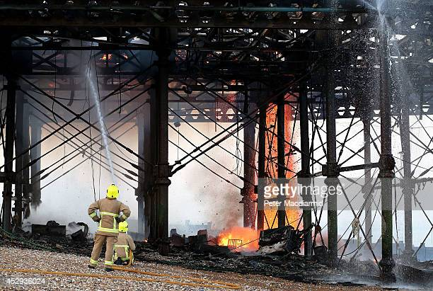 Debris falls as Fire Brigade officers damp down the remains of the arcade after a fire broke out on Eastbourne Pier on July 30 2014 in Eastbourne...