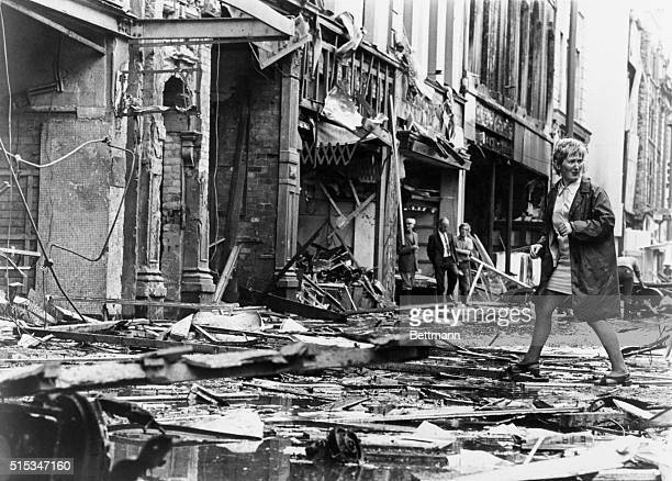 Debris fills street in section of center city here July 21st as female pedestrian looks over her shoulder while making her way through rubble...