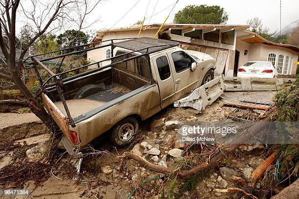 A debris flow damages homes and carries cars away on after heavy rains caused mudslides February 6 2010 in La Canada Flintridge California Large...