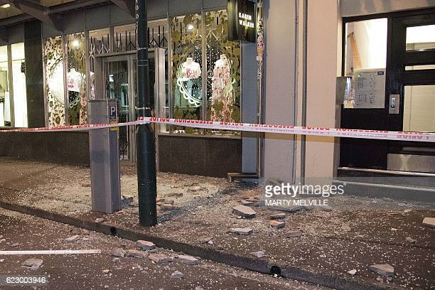 Debris from buildings are seen on a sidewalk past a cordon line in Wellington early on November 14 2016 following an earthquake centred some 90...