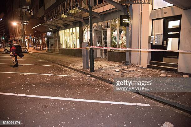 Debris from fallen concrete off buildings are seen on a sidewalk past a cordon line in Wellington early on November 14 2016 following an earthquake...