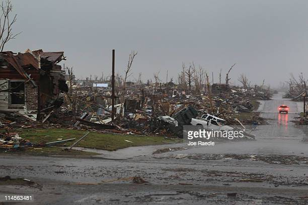 Debris from homes and cars are seen flung about after dozens of homes were destroyed and the search continues after 116 people where killed after a...