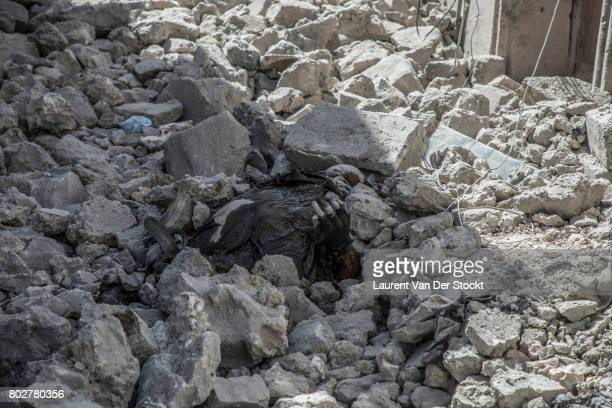 Debris from homes destroyed by bombings in the streets of the Old City of Mosul The dead body of an Islamic State fighter is partly under the rubble...