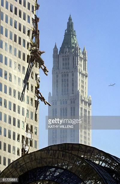Debris hangs from the side of the damaged American Express building as a plane passes near the Woolworth Building at the site of the World Trade...