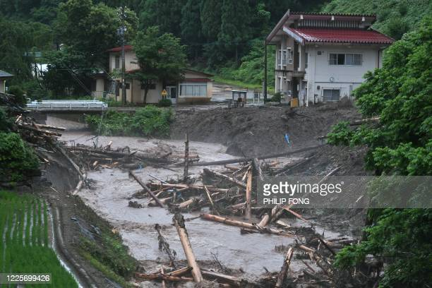Debris litter a village following heavy rains and flooding in the village of Takayama, Gifu prefecture on July 9, 2020. - Japanese emergency services...