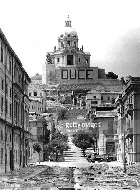 Debris litters the streets of Messina after the fall of Sicily Note the 'Duce' sign The Cathedral of Messina is in the background