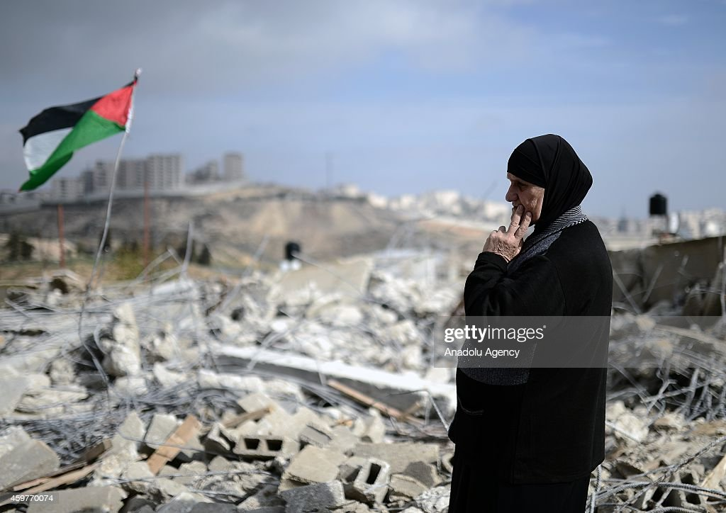 Debris of Palestinian Mustapha Hamdan's under-construction building, demolished by Israeli authority due to reason that the building does not have construction license, are seen in East of Jerusalem on December 01, 2014. A group of Palestinians planted a Palestinian flag on to debris to protest Israel's action.