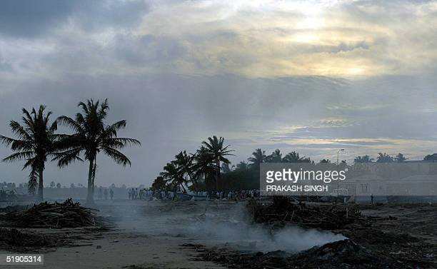 Debris of what once was a village burn as the sun sets at Velankanni beach some 365 km south of Madras 31 December 2004 The death toll in Asia's...