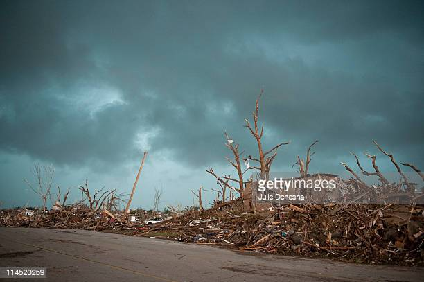 Debris surrounds a damaged home as a second storm moves in delaying rescue efforts on May 23, 2011 in Joplin, Missouri. A powerful tornado ripped...