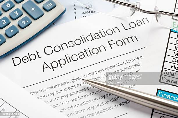 debt consolidation loan application form with pen, calculator - mergers and acquisitions stock pictures, royalty-free photos & images
