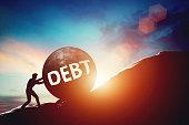 Debt problem. Man pushing huge concrete ball up hill.