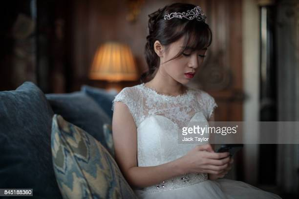 Debutante Annie Ding 20 from Hong Kong checks her phone at Leeds Castle during the Queen Charlotte's Ball on September 9 2017 in Maidstone England In...