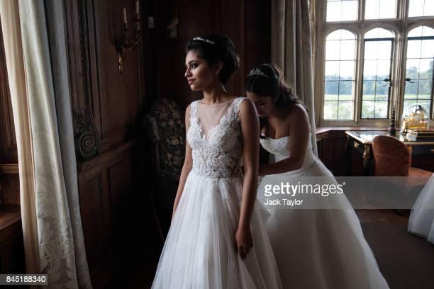 Debutante Carolina Lanz adjusts the dress of Shrishti Mishra 16 at Leeds Castle during the Queen Charlotte's Ball on September 9 2017 in Maidstone...