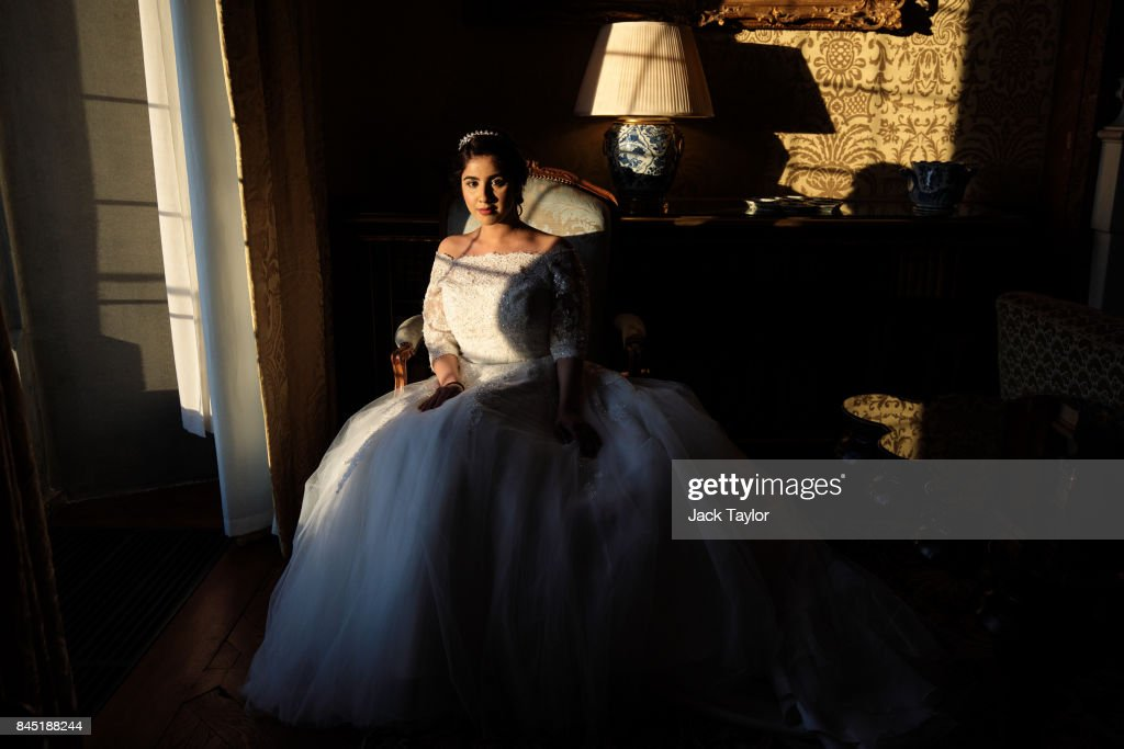 Debutante Fatima Khan, 19, from Buckinghamshire poses by a window at Leeds Castle during the Queen Charlotte's Ball on September 9, 2017 in Maidstone, England. In 1780 the first debutante's Ball was held by King George III to celebrate the birthday of his wife Queen Charlotte and raised money for a maternity hospital. Society girls were presented to the monarch and it became an annual event and important as a marriage market for the upper echelons of society. The London Season runs for six months of the year including sporting events, cocktail parties, dances and concerts and the Ball is the pinnacle of this season. After the present Queen terminated the practice of introducing debutantes at royal garden parties in 1957, Lady Howard de Walden followed by then editor of Tatler, Peter Townend, continued the tradition and on his death Peter nominated former debutantes Jennie Hallam-Peel and Patricia Woodall to take over running of The London Season. It is now focussed on raising money for children in need worldwide and the Queen Charlotte's Ball has been held in Shanghai and Dubai as well as various grand venues in London. This year the debutantes' gowns have been supplied by Berketex Brides and the cake, to which the debutantes curtsey, is made by Pretty Gorgeous Cakes.