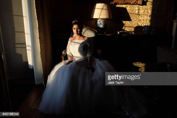 Debutante Fatima Khan from Buckinghamshire poses by a window at Leeds Castle during the Queen Charlotte's Ball on September 9 2017 in Maidstone...