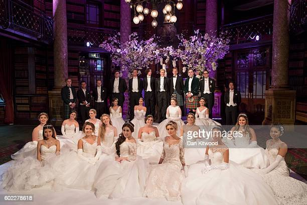 Debutantes and their escorts pose for pictures ahead of the Queen Charlotte's Ball at 'One Whitehall Place, The Royal Horseguards Hotel' on September...