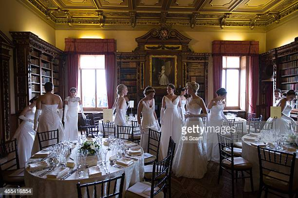 Debutantes check their seating allocation before the start of the Queen Charlotte's Ball at Highclere Castle on September 13, 2014 near Newbury,...