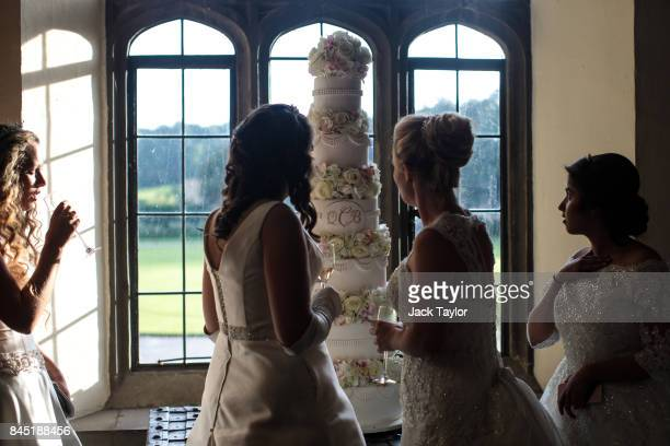 Debutantes drink champagne and look at the cake on display at Leeds Castle during the Queen Charlotte's Ball on September 9 2017 in Maidstone England...