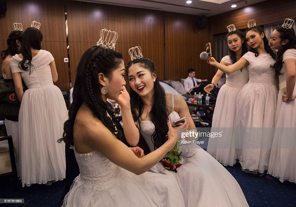 Debutantes from a local academy laugh as they get ready to take part in the Vienna Ball at the Kempinski Hotel on March 19, 2016 in Beijing, China. The ball, which is an event organized by the luxury Kempinski Hotel chain and the City of Vienna, brings together both Chinese and foreign members of the capital's elite class. Despite a slowing economy, private wealth has soared in China after decades of rapid growth. A record number of high net worth individuals and families has fuelled a market for luxury goods, services, and events catering to China's burgeoning elite class.