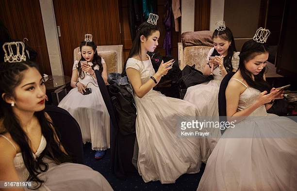 Debutantes from a local academy look at their mobile phones before taking part in the Vienna Ball at the Kempinski Hotel on March 19 2016 in Beijing...