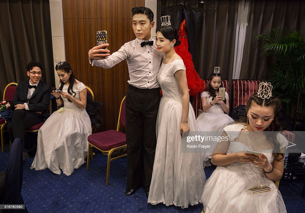 Debutantes from a local academy take pictures of themselves as they get ready to take part in the Vienna Ball at the Kempinski Hotel on March 19, 2016 in Beijing, China. The ball, which is an event organized by the luxury Kempinski Hotel chain and the City of Vienna, brings together both Chinese and foreign members of the capital's elite class. Despite a slowing economy, private wealth has soared in China after decades of rapid growth. A record number of high net worth individuals and families has fuelled a market for luxury goods, services, and events catering to China's burgeoning elite class.