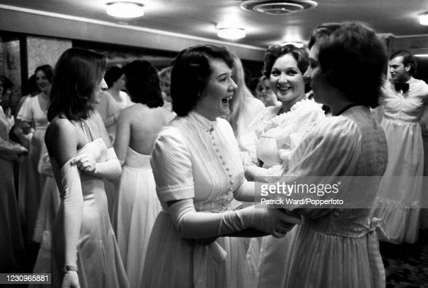 Debutantes greet each other at Queen Charlotte's Ball, at the Grosvenor House, Park Lane, London, England, with an interloping crossdresser , circa...