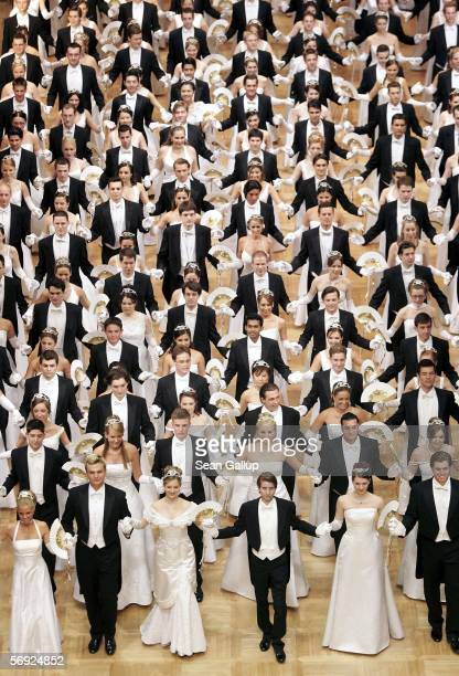 Debutantes walk out onto the dance floor for their first waltz at the 50th Vienna Opera Ball February 23 2006 in Vienna Austria