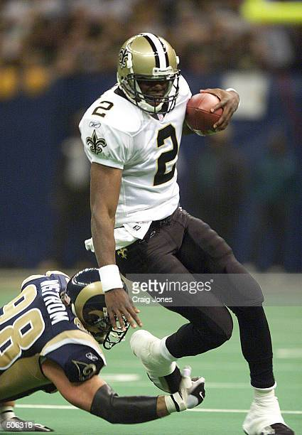 Aaron Brooks of the New Orleans Saints gets sacked by Grant Wistrom of the St Louis Rams during the first half of the St Louis Rams at New Orleans...