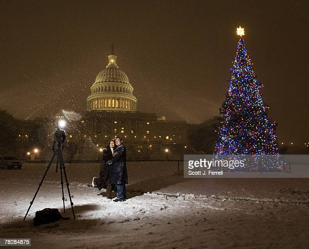 Husband and wife Paul and Cathy Le of Silver Spring Md take their picture during a snow shower in front of the the US Capitol Christmas tree a 55foot...