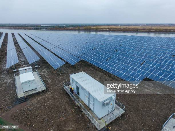 CIXI Dec 15 2017 Workers operate at a photovoltaic power station built on salinealkali soil in Cixi City east China's Zhejiang Province Dec 15 2017...