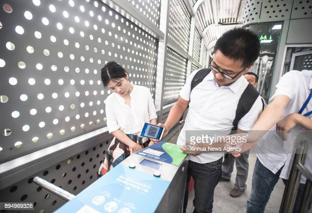 A passenger uses his cellphone to pay for the ticket at Wuchang Station of the Bus Rapid Transport in Wuhan capital of central China's Hubei Province...
