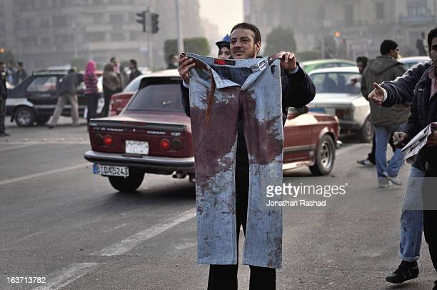 Dec 19, 2011: A protester holds pants of 21-year-old protester, Mohamed Mostafa, who was killed by police during clashes in Tahrir Square. More than...