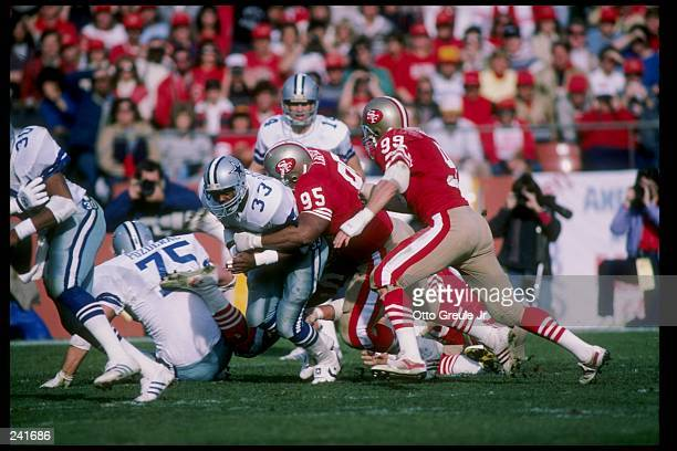 Running back Tony Dorsett of the Dallas Cowboys tries to run with the ball during a game against the San Francisco 49ers at Candlestick Park in San...