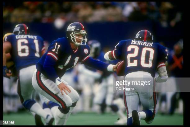Quarterback Phil Simms of the New York Giants hands off the ball to teammate running back Joe Morris during a game against the Green Bay Packers at...