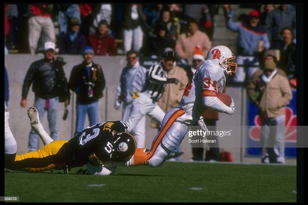 Running back Lars Tate of the Tampa Bay Buccaneers attempts to break the tackle of a Pittsburgh Steelers player during a game at Three Rivers Stadium in Pittsburgh, Pennsylvania. The Steelers won the game, 31-22. Mandatory Credit: Scott Hal