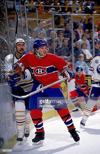 Paul Di Pietro of the Montreal Canadiens pushes a Buffalo Sabres player agiant the wall at the Marine Midland Arena in Buffalo New York The Sabres...