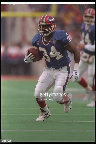 Running back Thurman Thomas of the Buffalo Bills runs with the ball during a game against the New England Patriots at Rich Stadium in Orchard Park,...