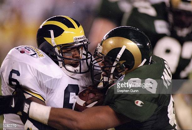 Tailback Tyrone Wheatley of the Michigan Wolverines grapples with Kareem Ingram of the Colorado State Rams during the Holiday Bowl game at Jack...