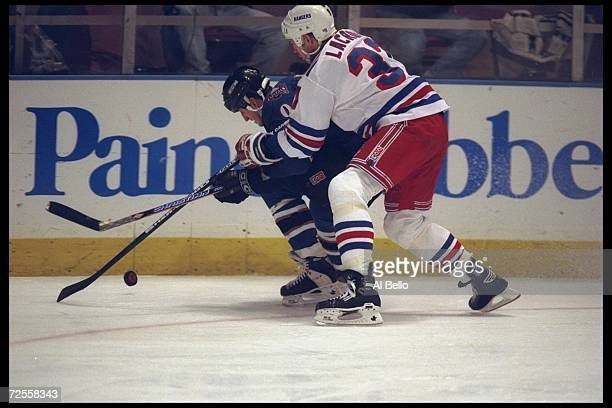 Leftwinger Daniel Lacroix of the New York Rangers and rightwinger Keith Jones of the Washington Capitals fight for the puck during a game at Madison...