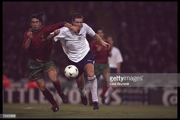 Paulo Alves of Portugal tangles up with Steve Howey of England during the friendly international at Wembley stadium which ended in a 11 draw