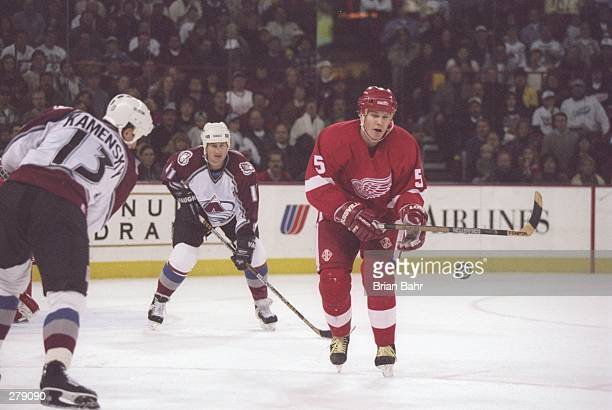 Defenseman Nicklas Lidstrom of the Detroit Red Wings moves the puck as Colorado Avalanche leftwinger Valeri Kamensky and rightwinger Keith Jones...