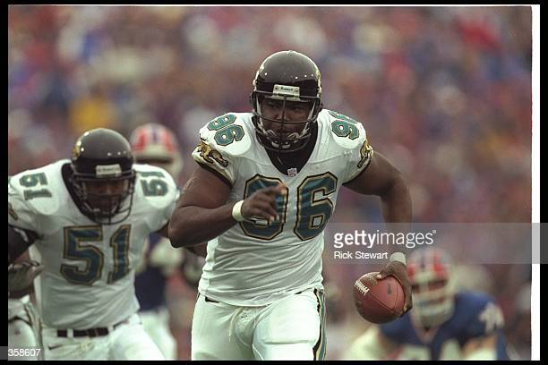 Defensive lineman Clyde Simmons of the Jacksonville Jaguars runs the ball for a touchdown during a playoff game against the Buffalo Bills at Rich...