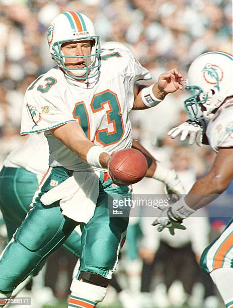 Dolphins quarterback Dan Marino hands the ball to Karim Abdul-Jabbar during the first quarter of game action at Oakland Alameda Coliseum in Oakland,...