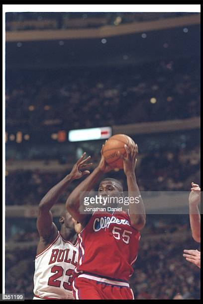Forward Lorenzen Wright of the Los Angeles Clippers moves the ball as Chicago Bulls guard Michael Jordan covers him during a game at the United...