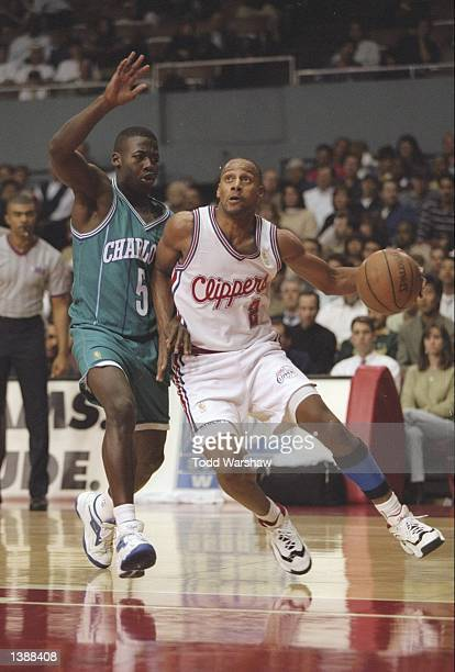 Guard Pooh Richardson of the Los Angeles Clippers drives past guard Anthony Goldwire of the Charlotte Hornets at the Los Angeles Sports Arena in Los...